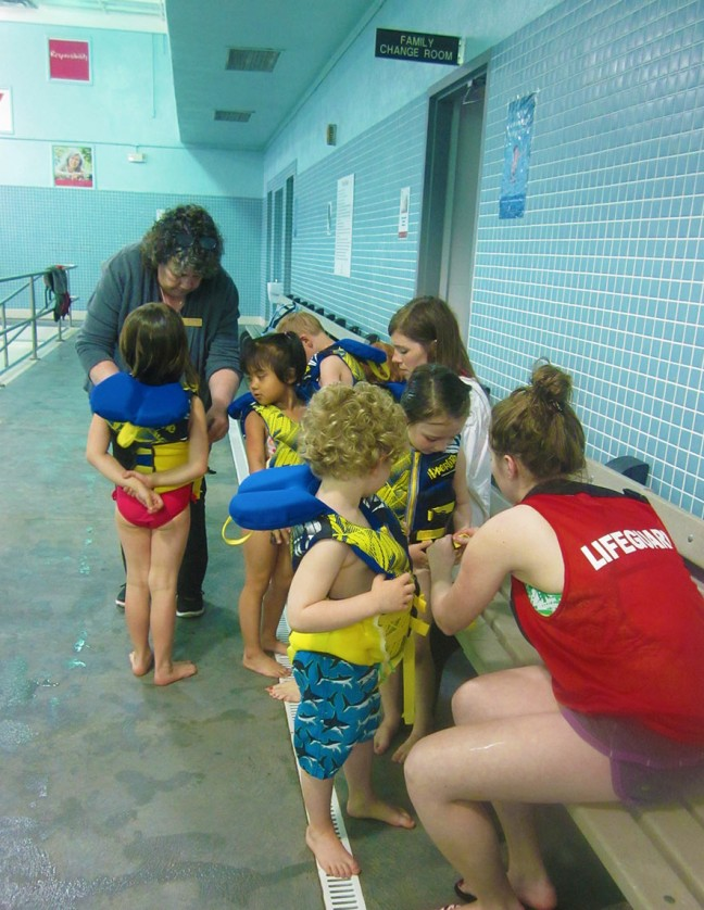 All hands are on deck to help with life jackets.
