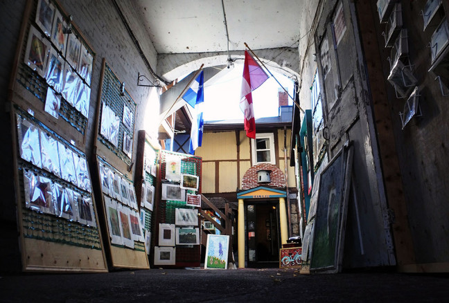 A variety of prints, paintings, and postcards are hung in the alleyway. The cases close at night to look like French windows.
