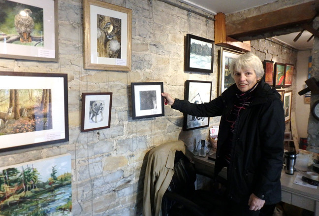 Chris Perry stands with her graphite drawing of a raven, whose curious, intelligent eye draws attention from viewers.