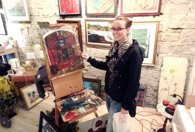 Queens student Elizabeth Gibson Crowder stands next to a painting-in-progress by David Dossett.