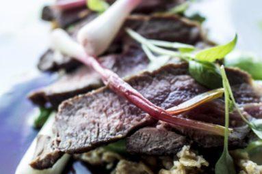 Ontario Lamb Loin: Pan seared, sautéed romano bean, Mill Creek peas, spring onion, pickled ramps, lamb jus, wild leek + goat cheese croquette, wild leek out, smoked oats.